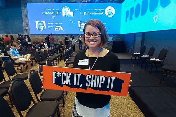 woman holding sign that says 'Fuck it, ship it'